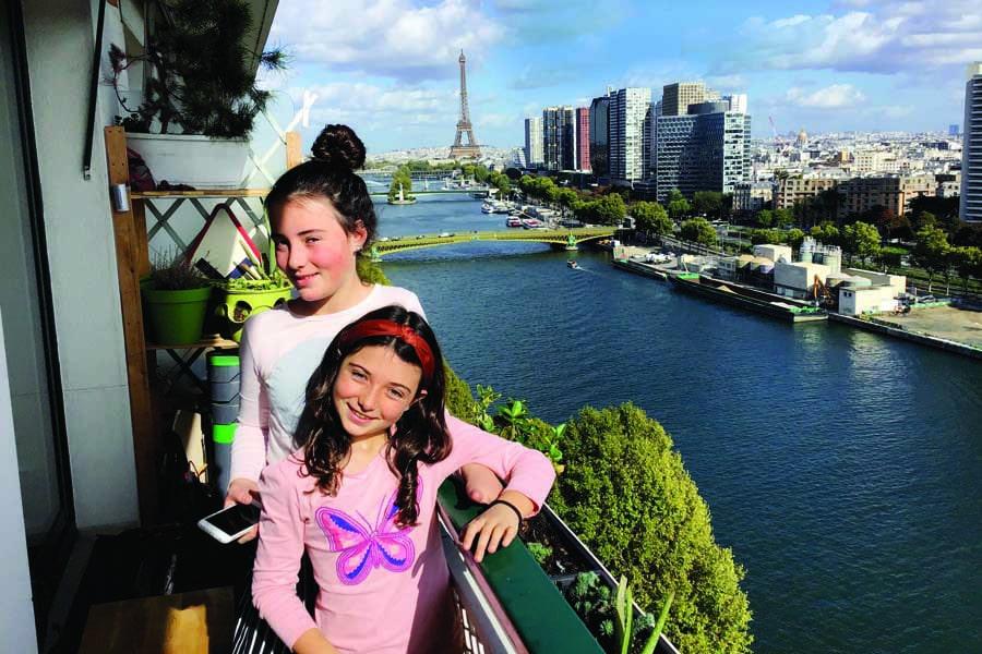 mila and freya on the balcony of their paris apartment