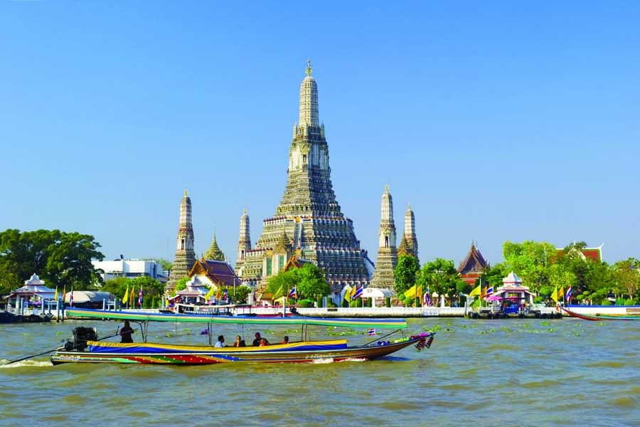 a longtail boat passing wat arun rajwararam in bangkok