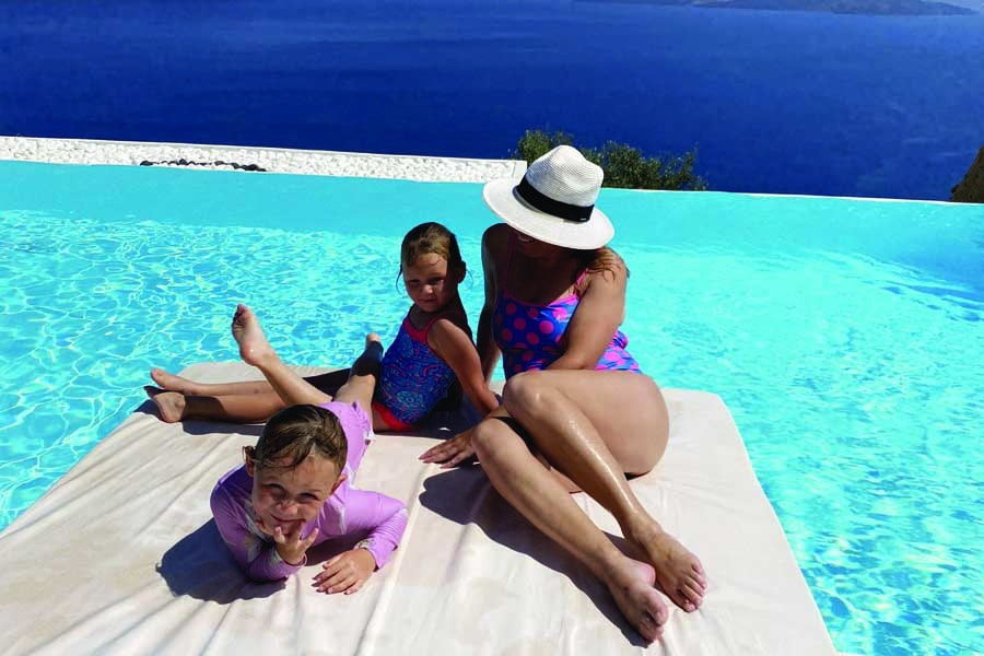 relaxing by the pool at adronis luxury suites located cliffside in santorini