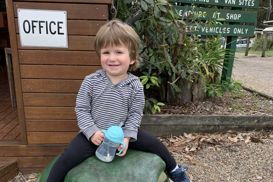 oliver sitting on a frog at durras lake north holiday park