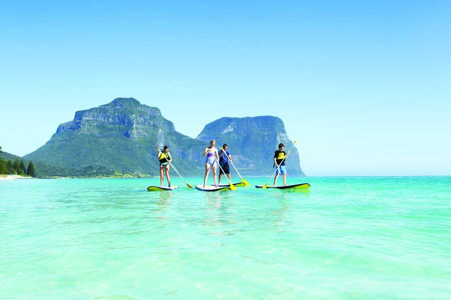a family stand up paddleboarding at lagoon beach on lord howe island. image destination nsw