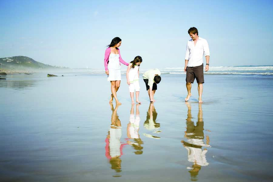 a family walking on fairhaven beach along the great ocean rd. image visit victoria
