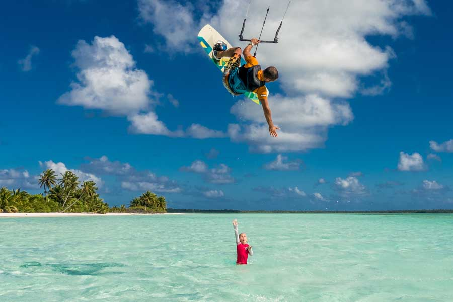 a girl waving at a kite surfer in the cocos keeling islands