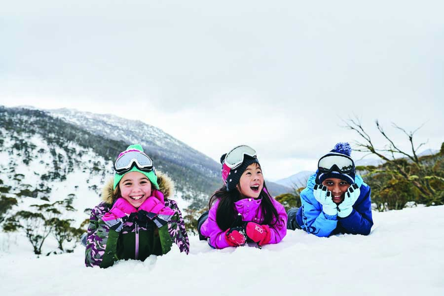 children having fun in the snow at thredbo. image destination nsw