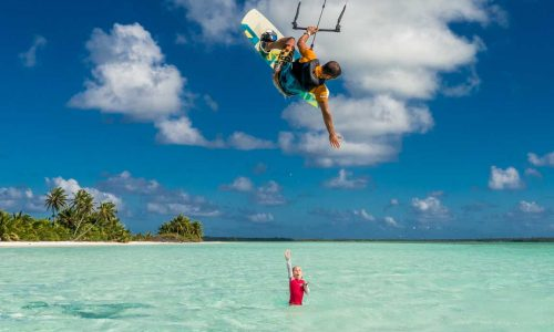 feature a girl waving at a kite surfer in the cocos keeling islands